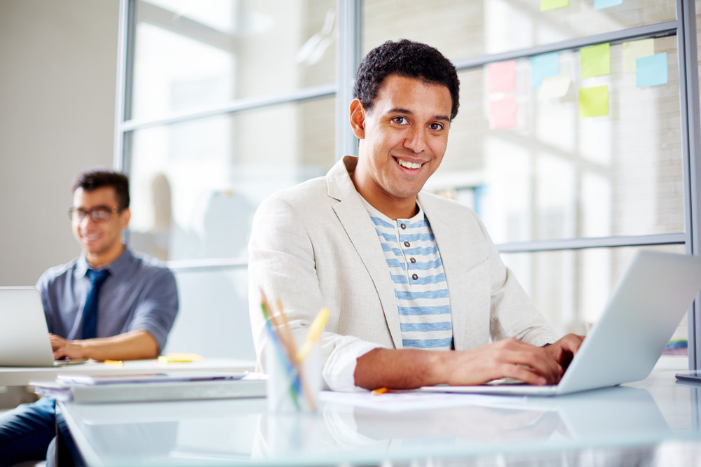 Successful Businessman Networking In Office With Colleague On Background
