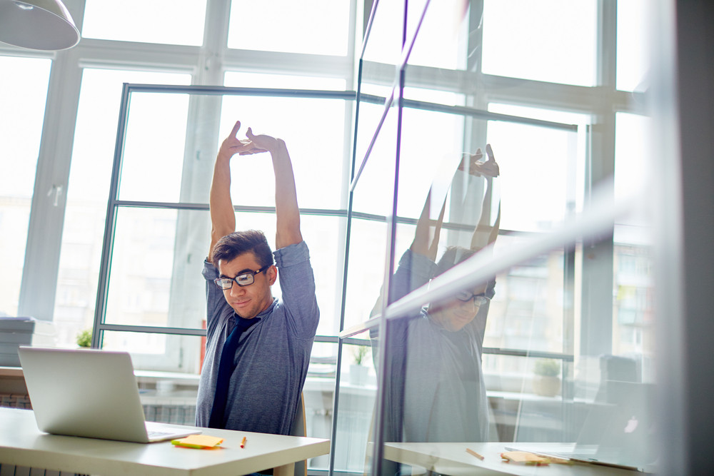 Young Businessman With His Arms Stretched Upwards Looking At Laptop Display