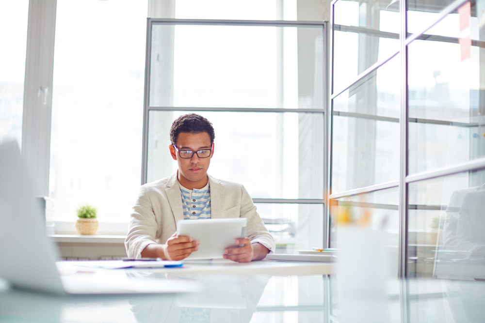 Attractive Employee Using Digital Tablet In Office