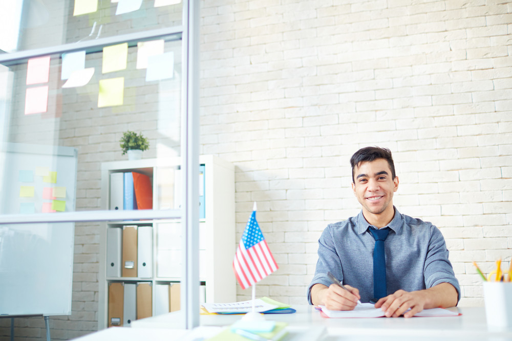 Happy Young Businessman Looking At Camera In Office