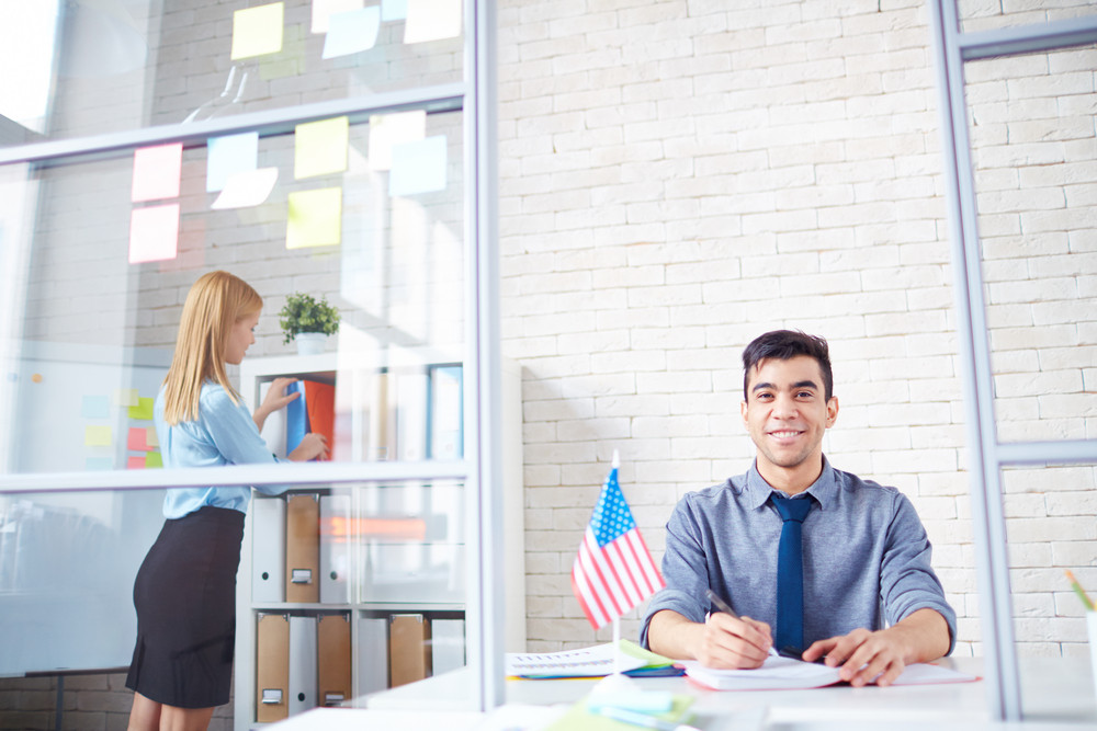 Happy Young Employer Looking At Camera At Workplace