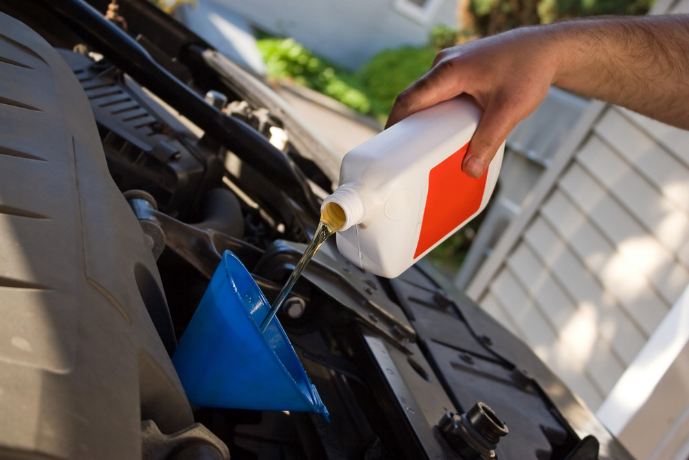 A backyard mechanic pours motor oil into the engine at the end of an oil change.  Home maintenance is becoming more popular during hard economic times.