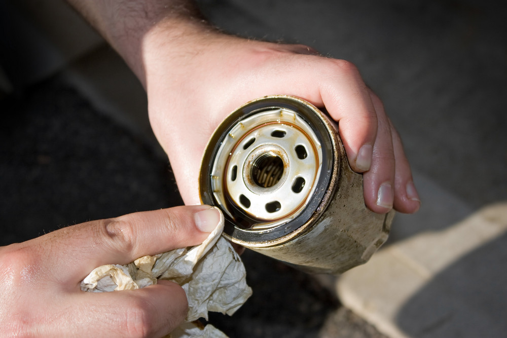 A backyard mechanic wipes the seal of  a slightly used oil filter to reuse it for an additional 3000 miles.  Others prefer to replace them each and every oil change.