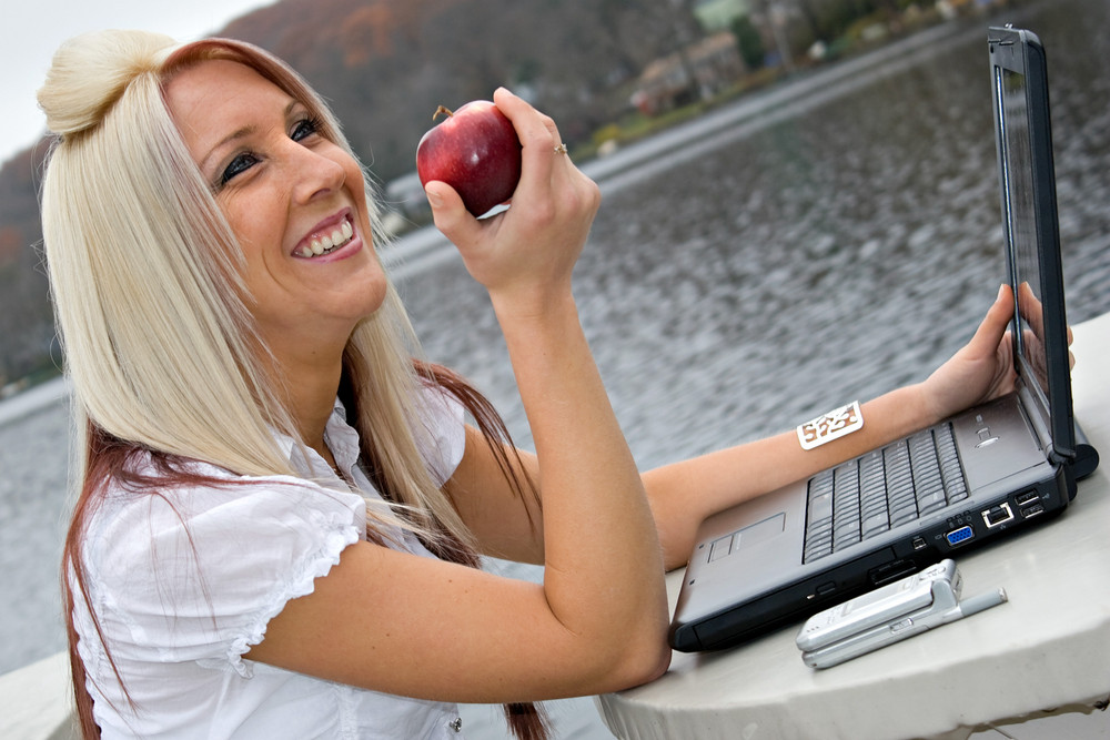 A beautiful young blonde woman in a mobile business setting eating a red apple.