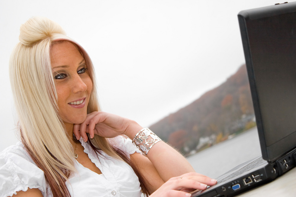 A beautiful young blonde woman in a mobile business setting with her laptop.