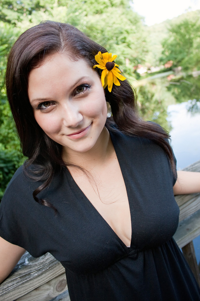 A beautiful young brunette woman wearing a black eyed susan wildflower in her hair.