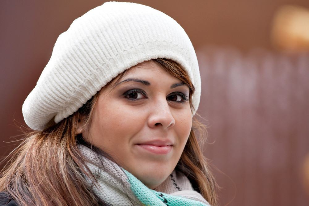 A beautiful young Hispanic woman with a smile on her face wearing a winter buret style knit hat.