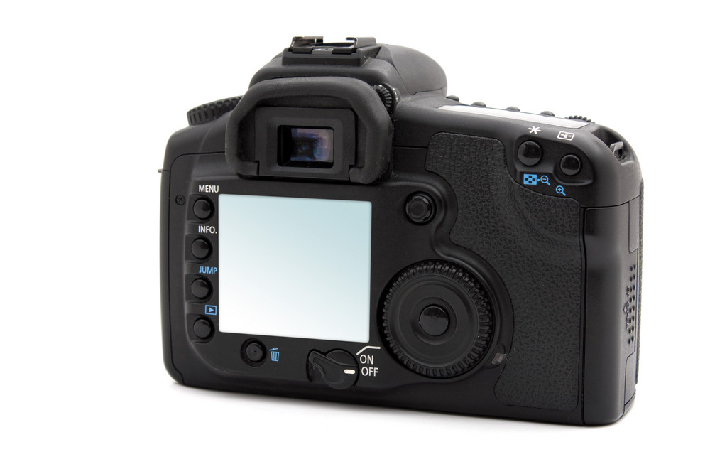 A black digital SLR camera isolated on white.  The clipping path is included for easy isolation of the LCD screen area.