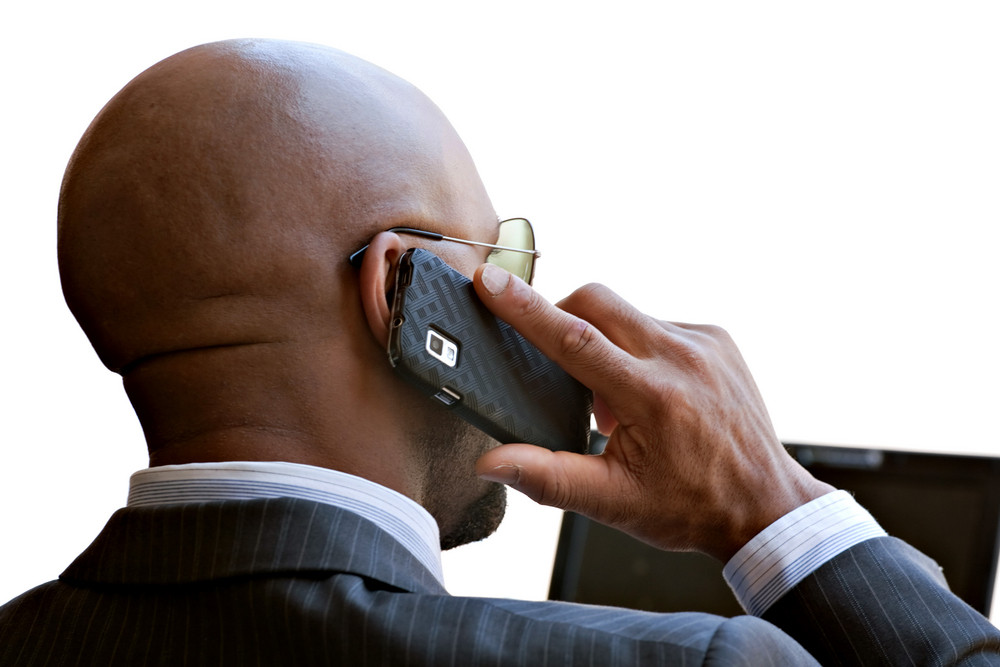 A business man in his early 30s talking on his smart phone and working on his laptop or netbook computer.