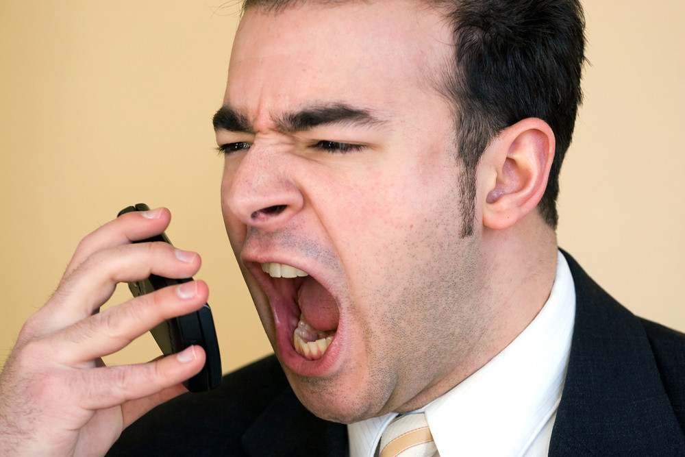 A business man is furiously screaming into his cell phone.