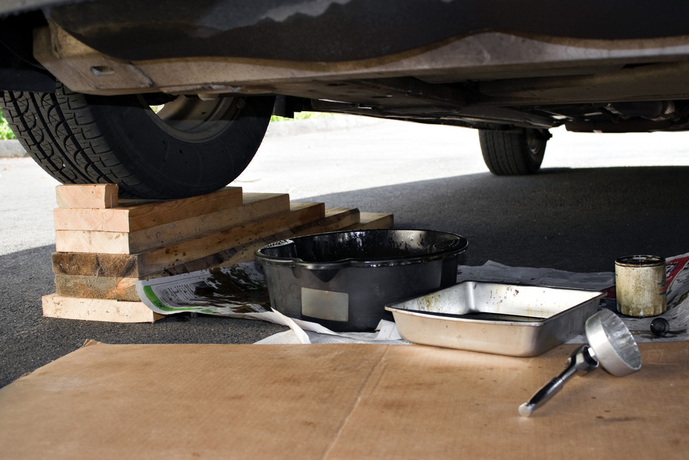 A car is parked up on ramps for regular repairs or maintenance on the vehicle.  Oil pans and wrench are ready to complete the job.