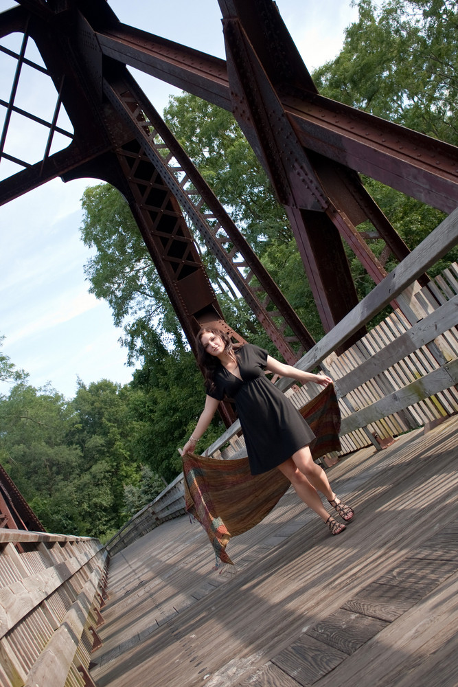 A carefree brunette girl walking along a bridge with a scarf blowing in the breeze.