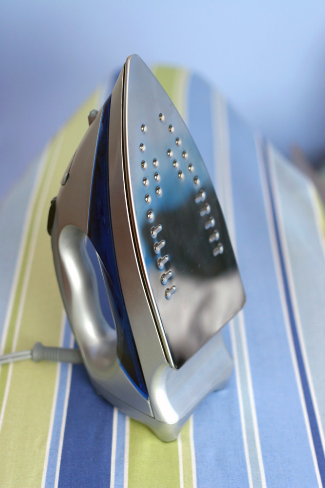 A closeup of a basic household iron set on top of an ironing board.