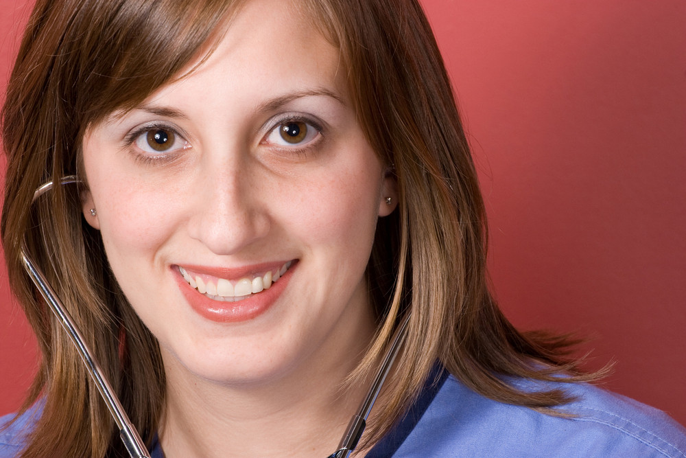 A closeup of a nurse smiling while using her stethoscope.