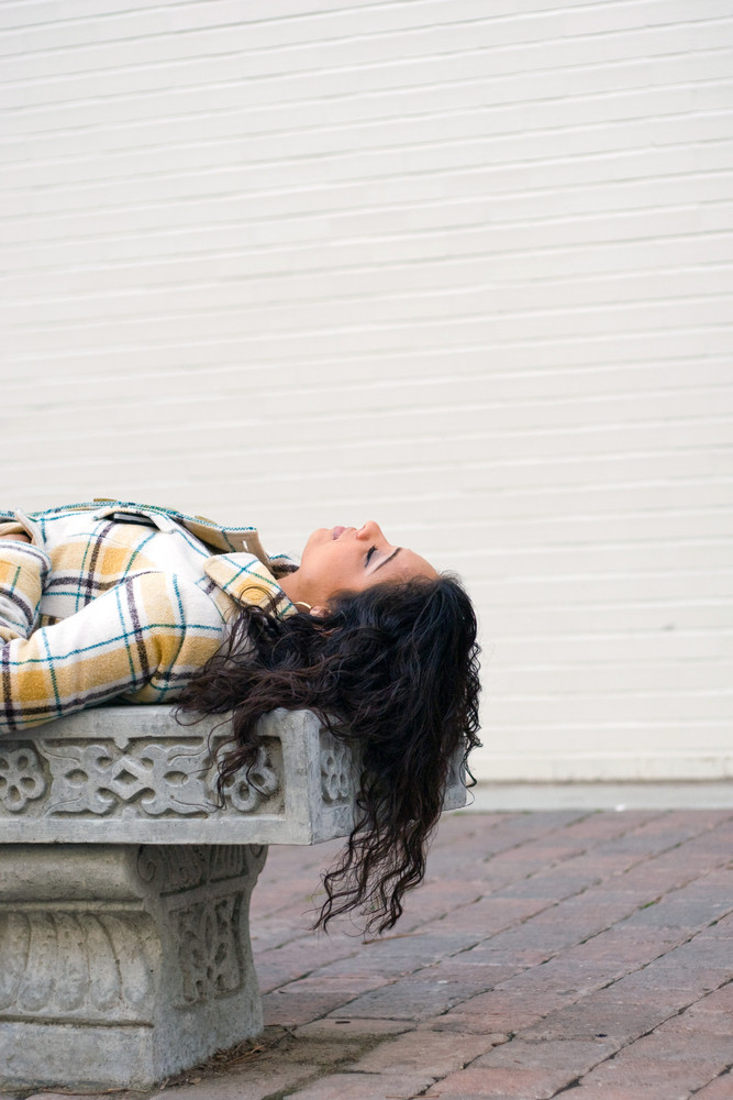 A closeup of a pretty Indian woman laying on a bench outdoors.