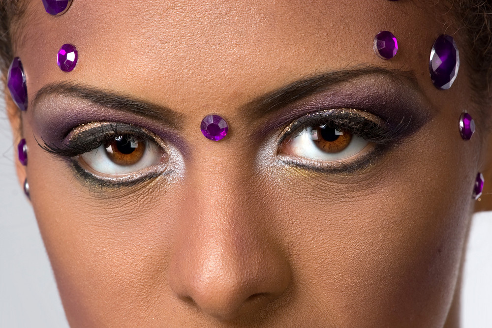 A closeup of a womans eyes with extravagant and glamorous makeup and gemstones looking very seductive.