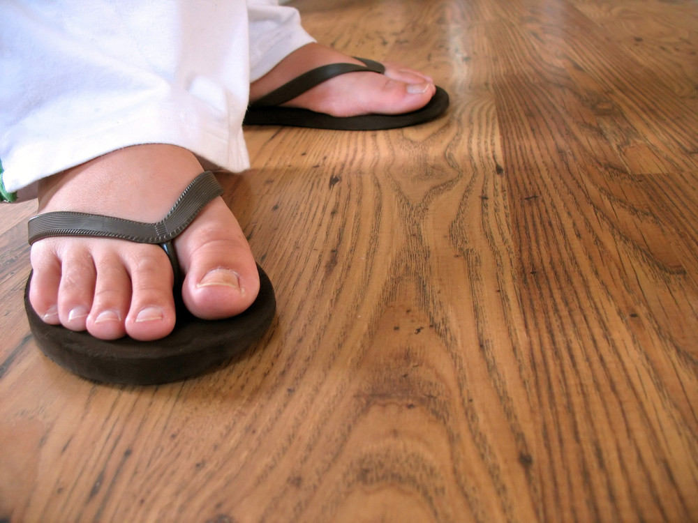 bcb4c99be2708 A closeup of a woman s feet wearing some black flip flops. Royalty ...