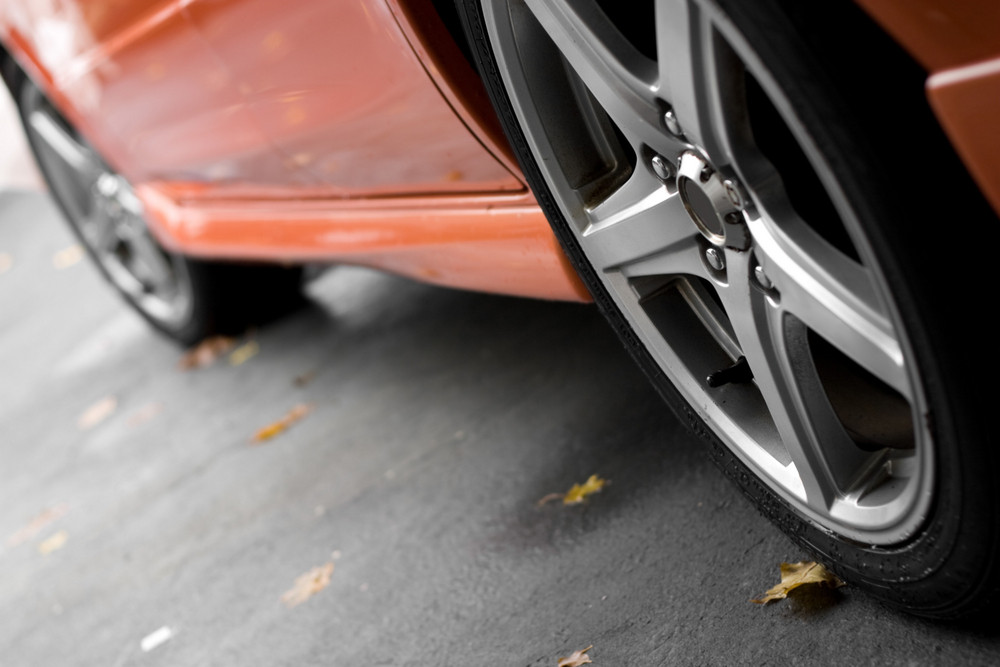 A closeup of the custom rims on a modern sports car with plenty of copyspace. Shallow depth of field.