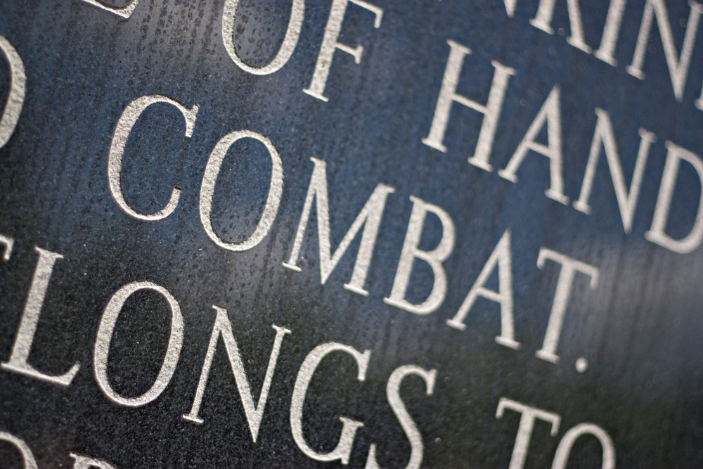 a closeup of the word combat engraved on a war memorial plaque