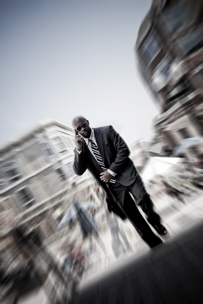 A confident business man walking through the city while talking on his smartphone. Zoom blur vignetting and desaturated toning for added effect.