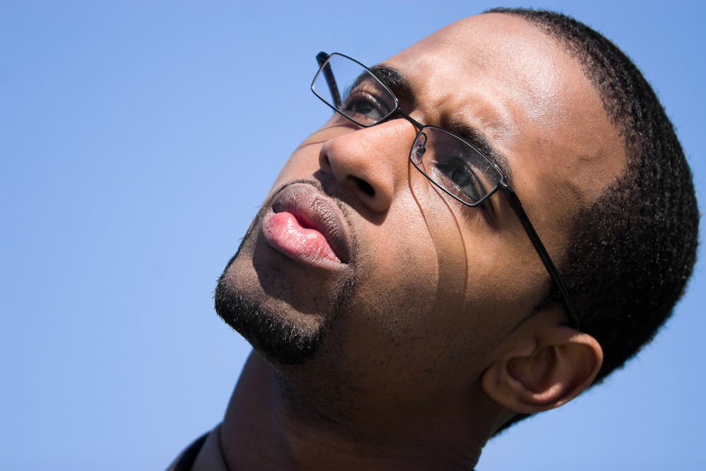A contemplative African American man wearing glasses isolated over a blue background.