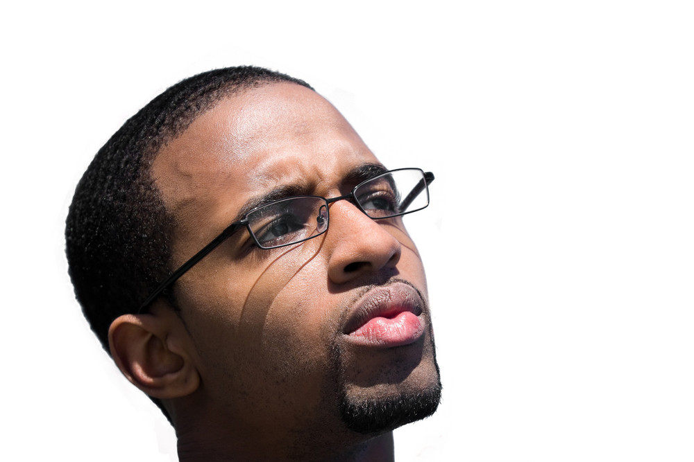 A contemplative African American man wearing glasses isolated over a white background.
