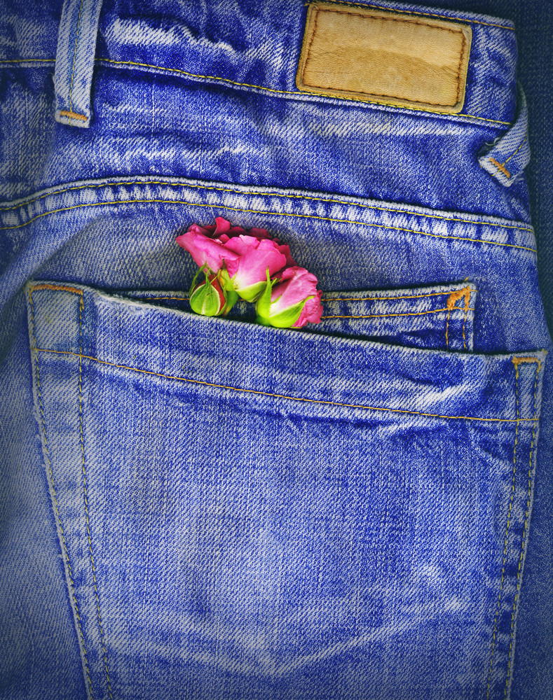 A Couple Of Roses Tucked In A Denim Pocket. Conceptual Image For Love