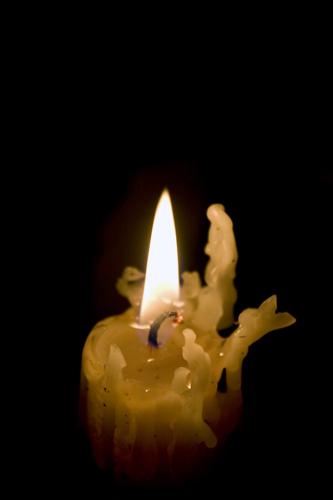 A creepy old candlestick burns on as it melts down little by little.