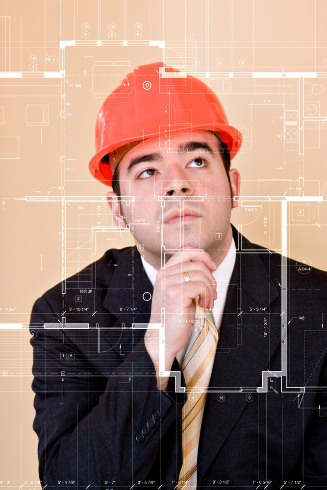 A custom home builder or architect thinks as he examines the blueprints on the clear glass display in front of him.