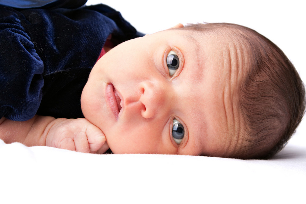 A cute newborn baby girl laying on a white backdrop.