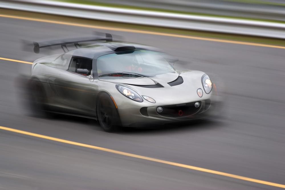 A fast silver sports car speeding down the road. Slight motion blur.