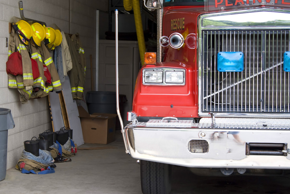 A fire truck is parked in the bay with all of the fire fighting equipment and gear ready to go.