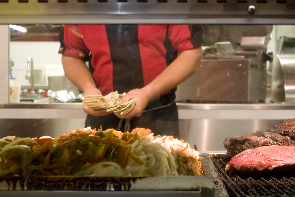 A food vendor or restaurant owner counts money at the end of the business day.