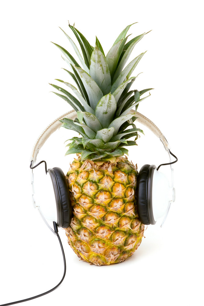 A fresh ripe pineapple wearing headphones isolated over a white background.