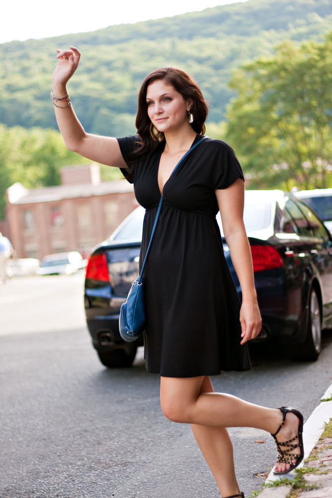 A gorgeous brunette woman hails a cab at the side of the road in the city.