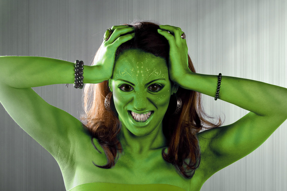 A green alien or Martian woman posing over a silver brushed metal backdrop.