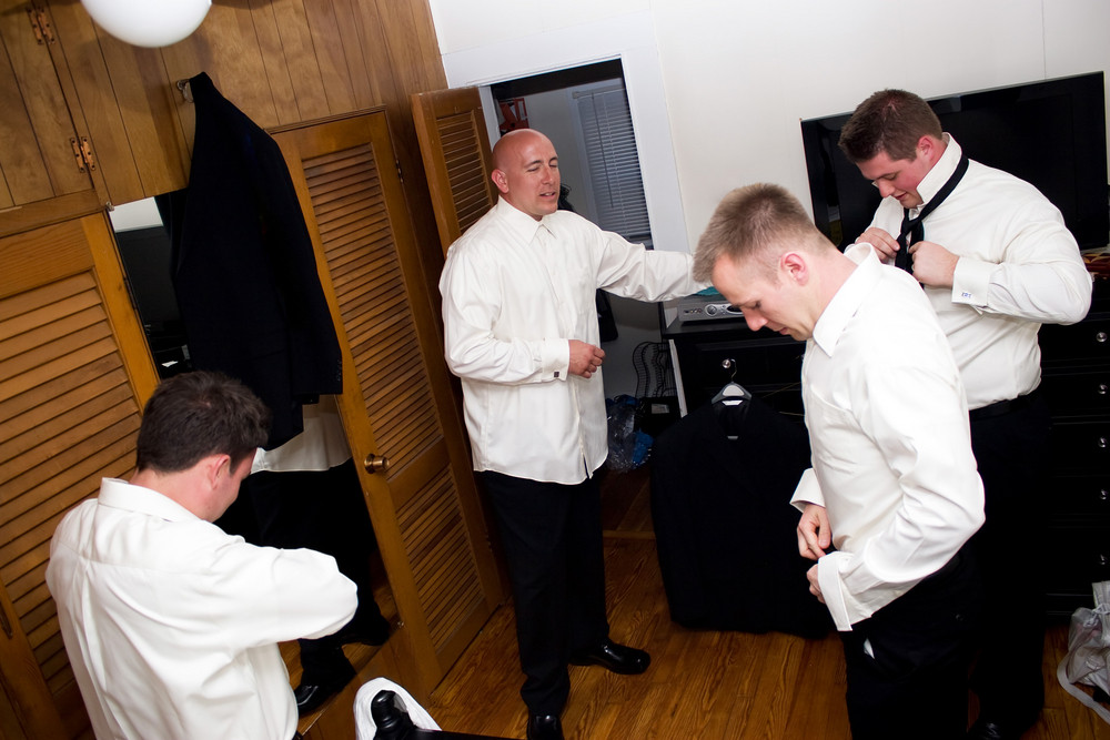 A groom along with his three groomsmen getting dressed and ready for the wedding.