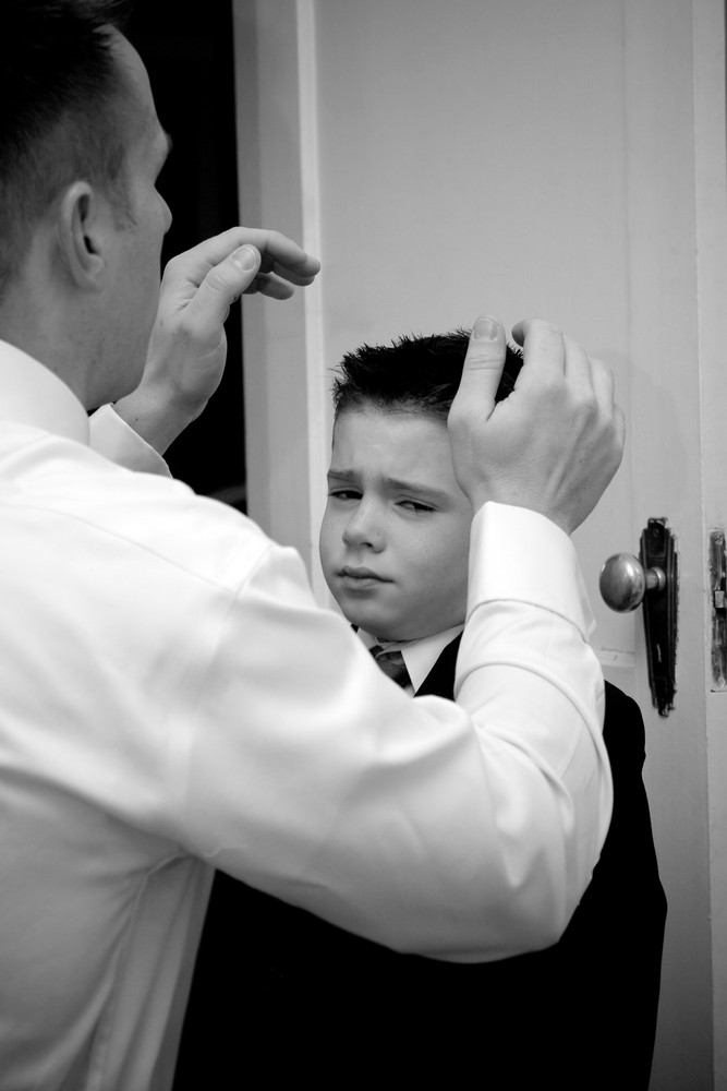 A groom helps his son get ready by doing his hair.