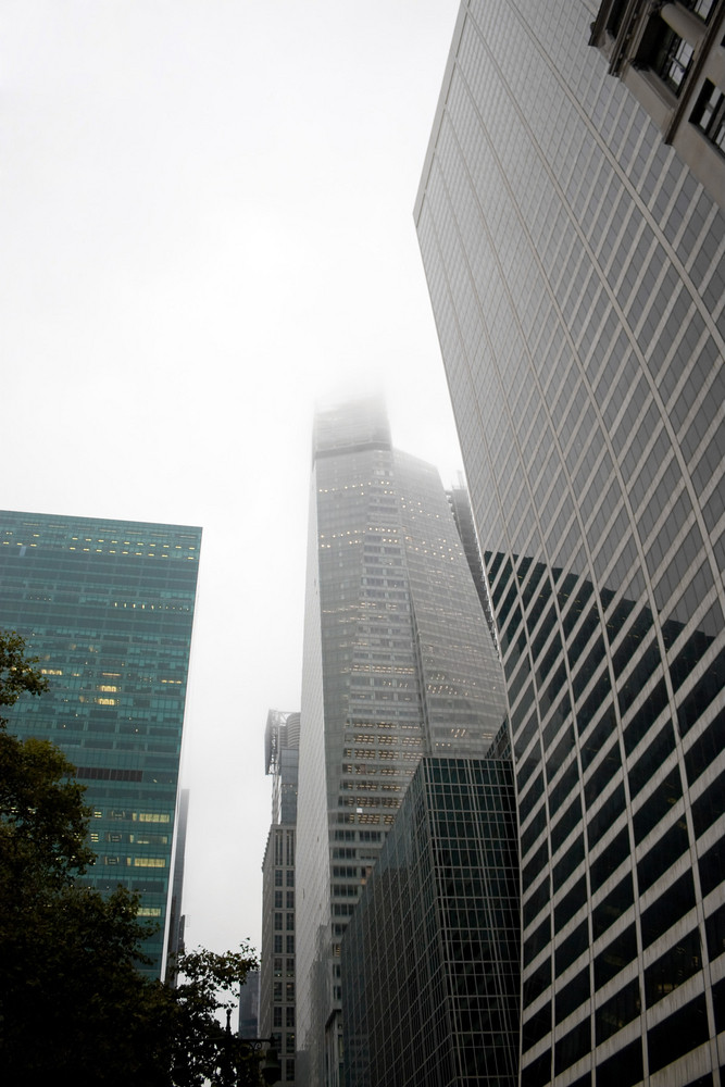 A group of city skyscraper buildings on a gloomy and foggy overcast day.