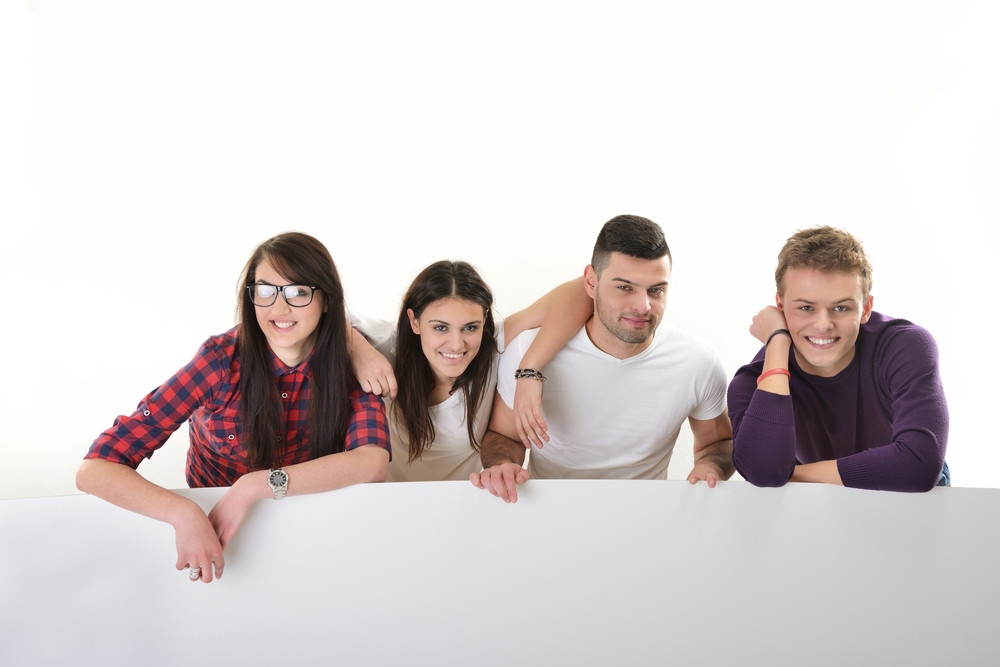 A group of happy young people isolated on white holding an empty banner