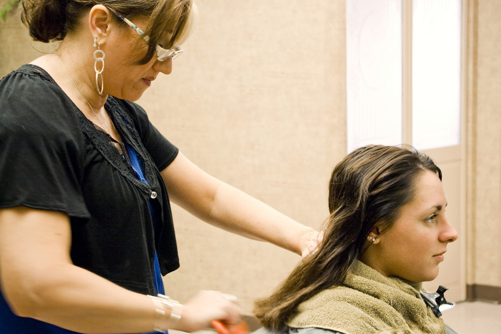A hairdresser working on a clients hair at the salon.