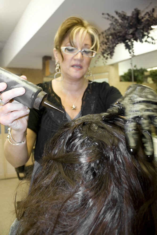 A hairdresser working on a clients hair color at the salon