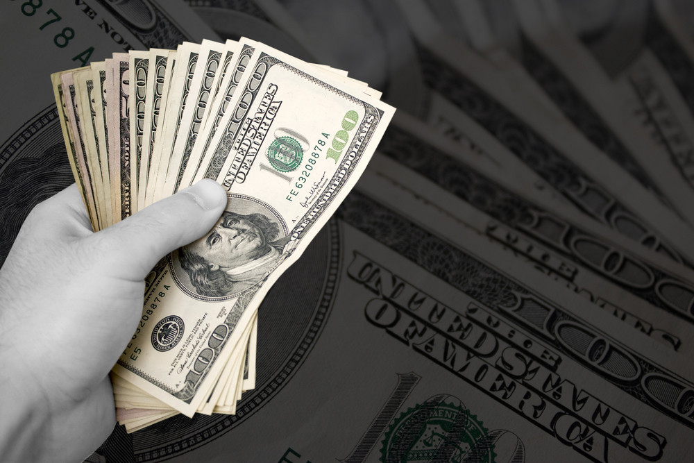 A handful of cash isolated over a gold background.  The money has selective color, and the rest of the image is in black and white.