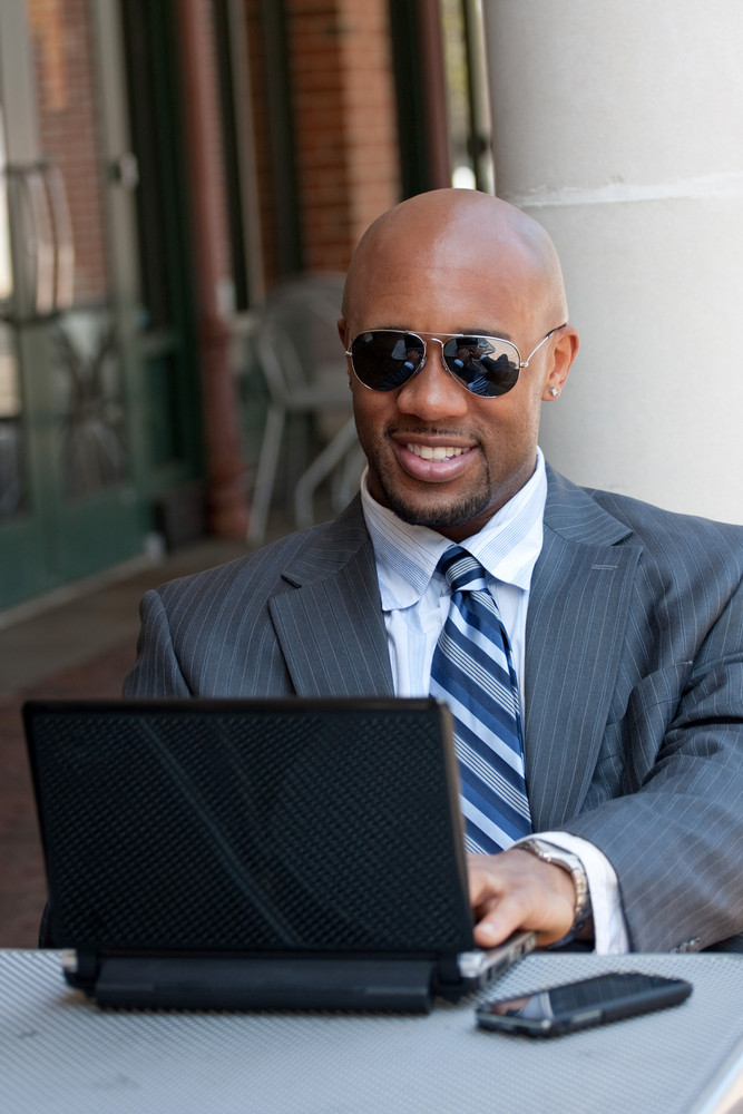 A handsome African American business man in his early 30s working on his laptop or netbook computer with his cell phone nearby.