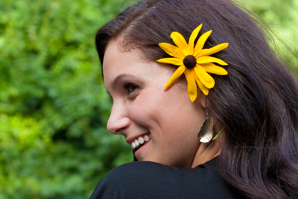 A happy and beautiful young brunette woman wearing a black eyed susan wildflower in her hair.