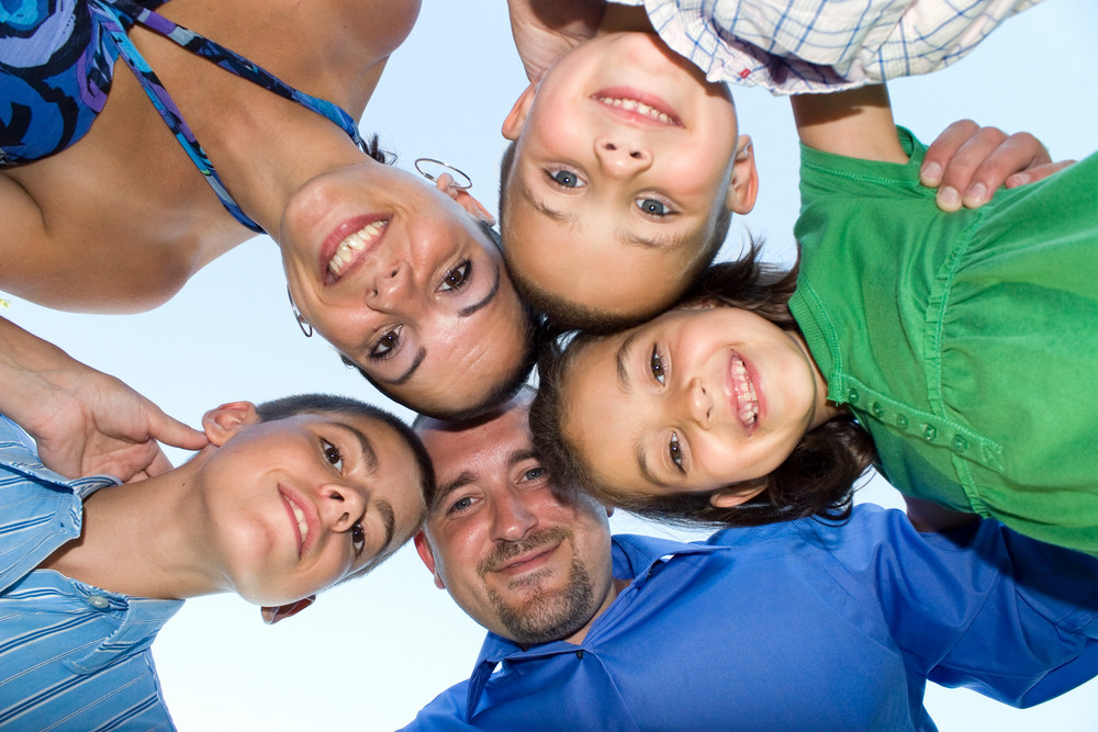 A happy family posing in a group huddle formation.  Shallow depth of field.
