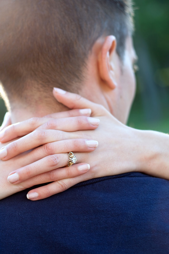 A happy woman hugs her fiance by placing her hands around his neck. Shallow depth of field with focus on the diamond engagement ring.
