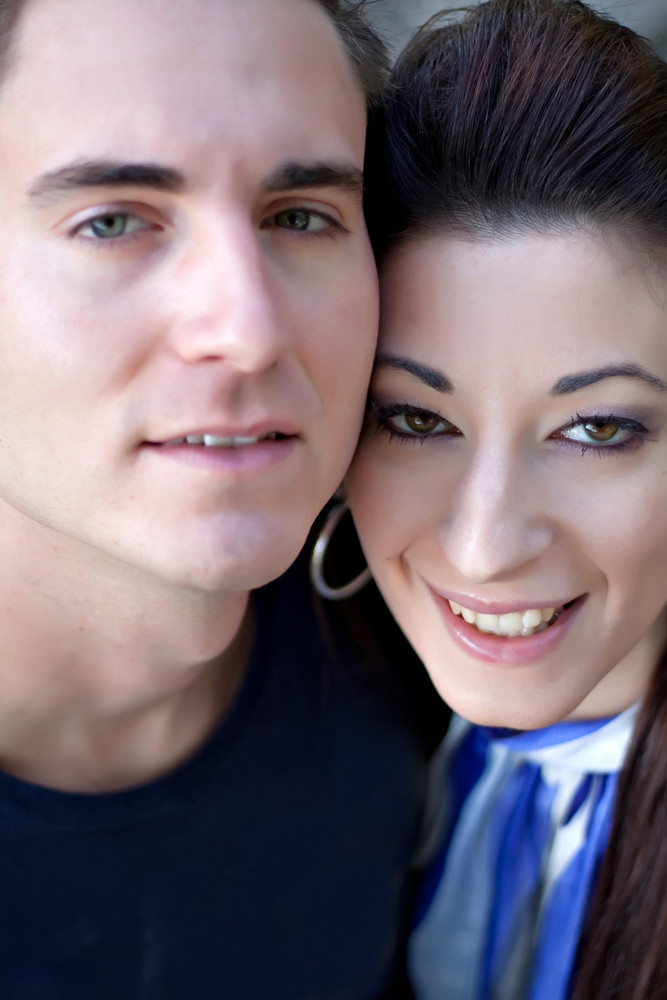 A happy young couple in their mid 20s smiling with their heads close together. Shallow depth of field with sharpest focus on the woman.