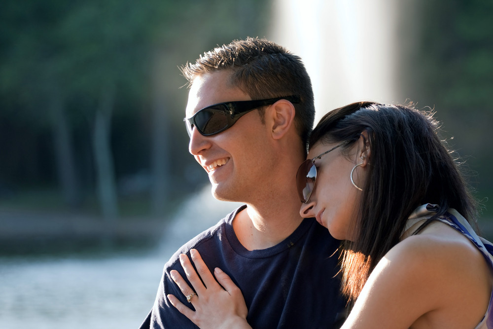 A happy young couple in their mid 20s wearing sunglasses with the girl leaning on the guys shoulder.