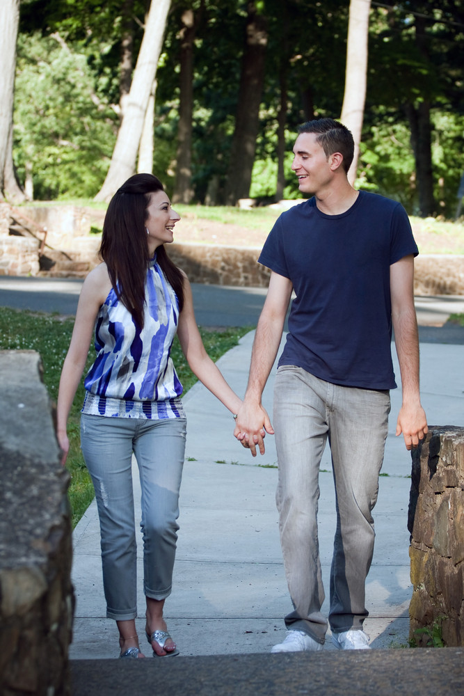 A happy young couple in their mid twenties smiling at each other during a walk through the park.